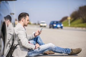 Man Sitting Near Car Needs Roadside Assistance